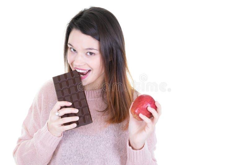 Retrato de um chocolate de mordedura da jovem mulher moreno com maçã vermelha à disposição no fundo branco imagens de stock