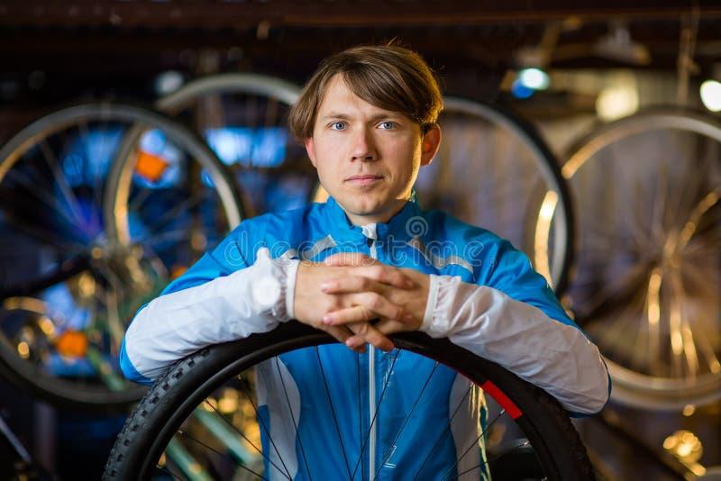 Retrato de um ciclista na garagem com as bicicletas atrás dele foto de stock