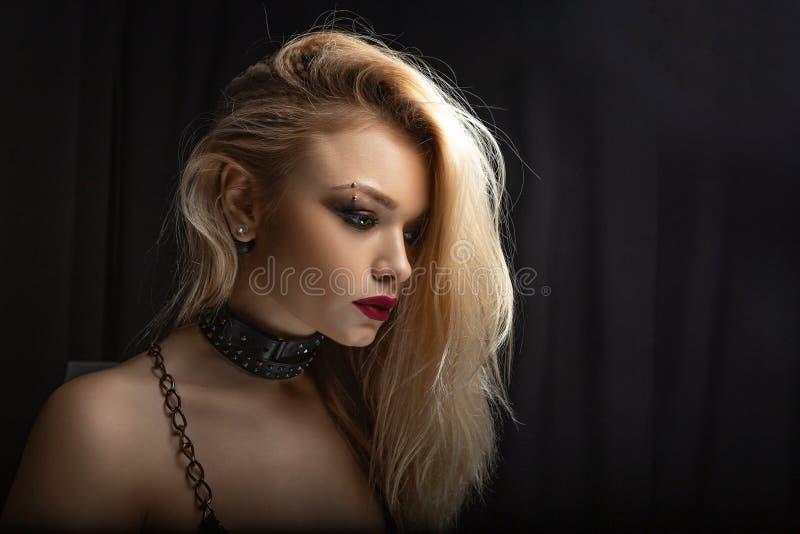 Retrato de um close-up louro bonito, em um fundo escuro fotos de stock