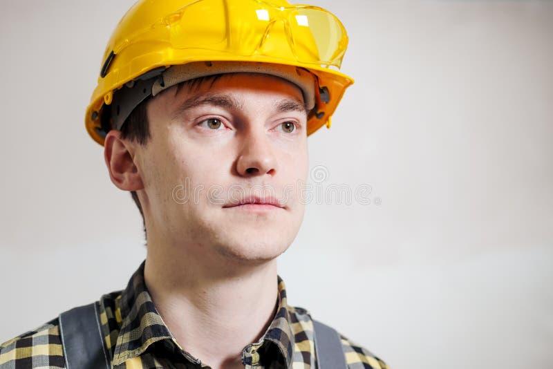 Retrato de um construtor e de um reparador masculinos novos em um capacete amarelo na perspectiva de uma parede fotos de stock royalty free