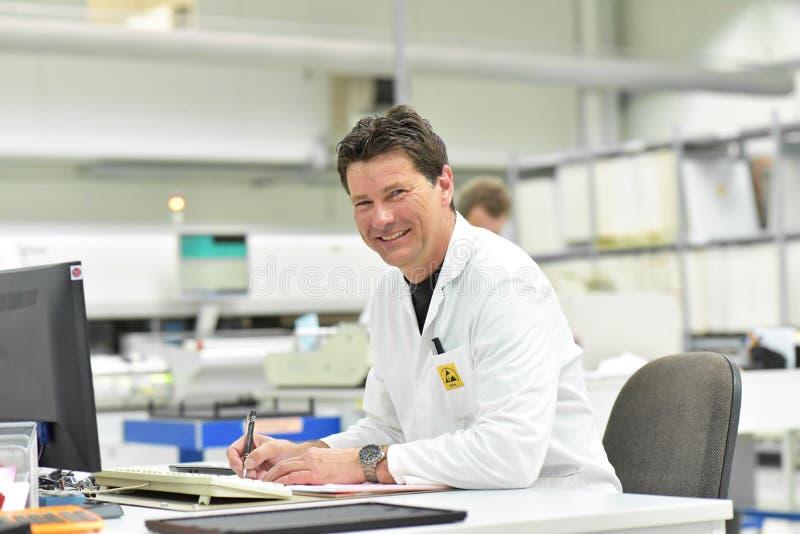 Retrato de um coordenador amigável do trabalhador em uma fábrica moderna em t foto de stock