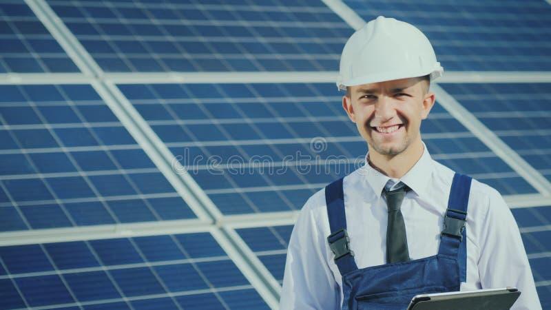 Retrato de um coordenador novo bem sucedido no fundo de uma central elétrica de energias solares foto de stock royalty free