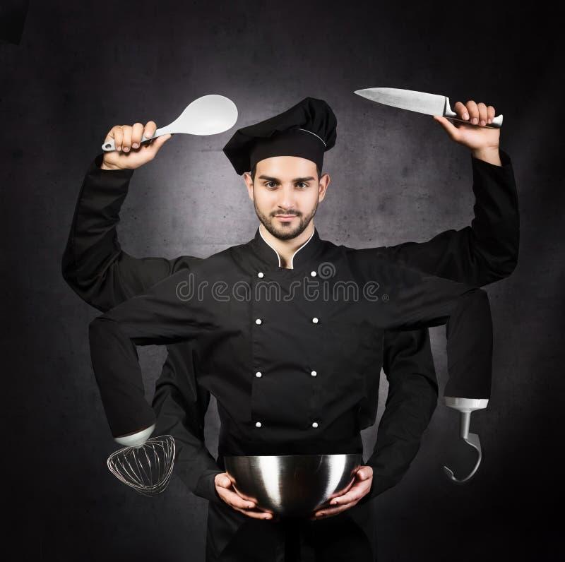 Retrato de um cozinheiro chefe com muitas mãos no fundo cinzento Cozinha m fotografia de stock