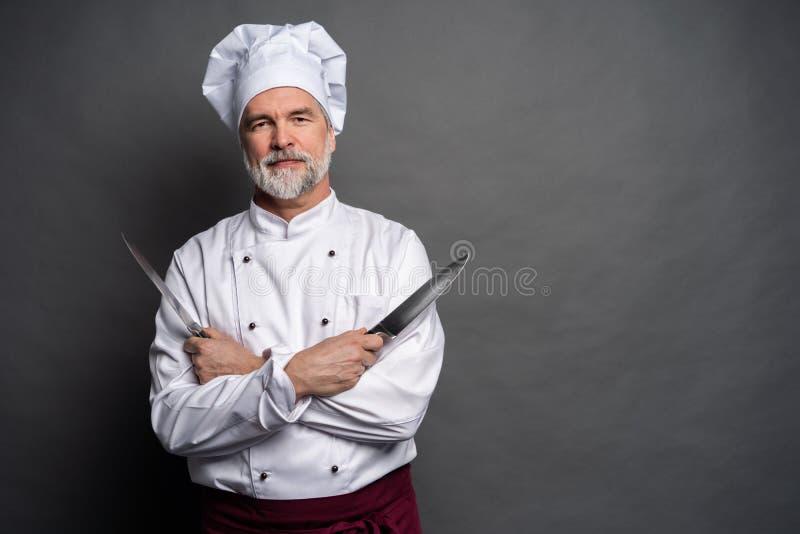Retrato de um cozinheiro maduro do cozinheiro chefe que mant?m facas isoladas em um fundo preto imagens de stock