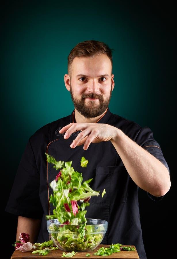 Retrato de um cozinheiro masculino considerável do cozinheiro chefe que faz a salada saboroso em um fundo borrado de água-marinha imagem de stock royalty free