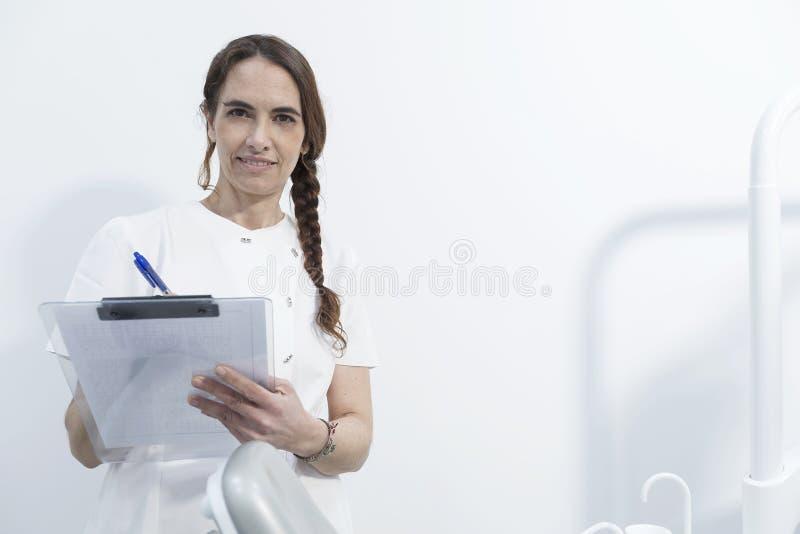 Retrato de um dentista da jovem mulher, gravando no original, no CCB foto de stock royalty free