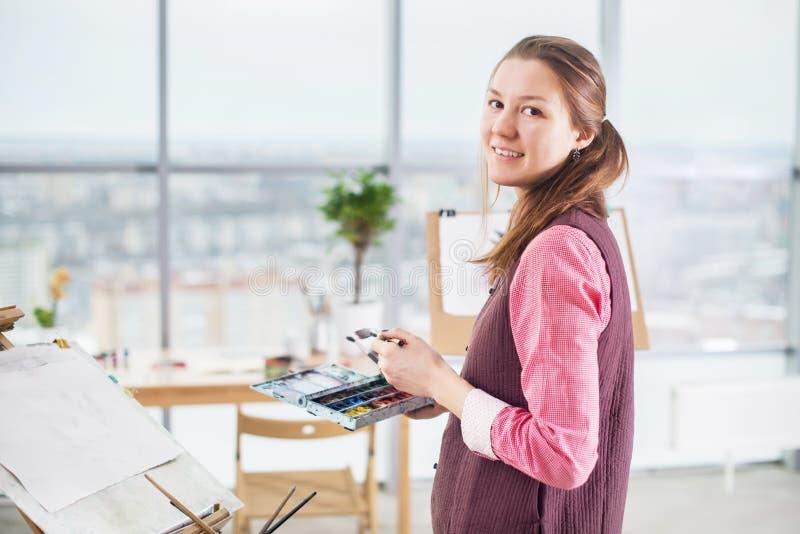 Retrato de um desenho do pintor da jovem mulher com a paleta da aquarela na armação de utilização de papel foto de stock