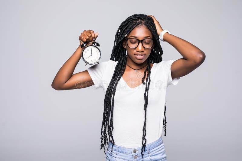 Retrato de um despertador afro-americano novo chocado da terra arrendada da mulher isolado sobre o fundo cinzento imagem de stock royalty free