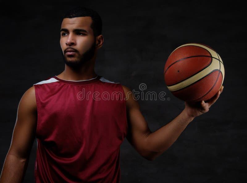 Retrato de um desportista afro-americano Jogador de basquetebol no sportswear com uma bola imagem de stock