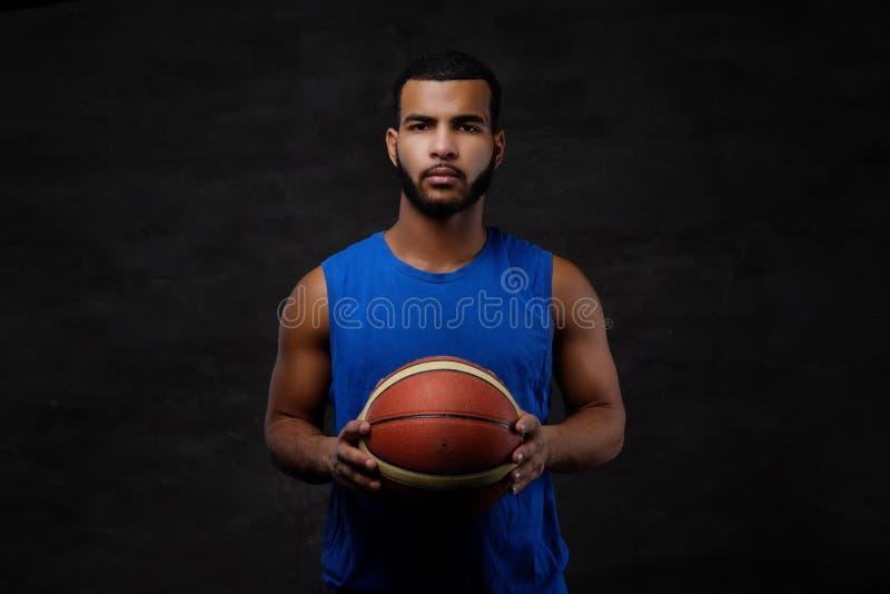 Retrato de um desportista afro-americano Jogador de basquetebol no sportswear com uma bola imagens de stock