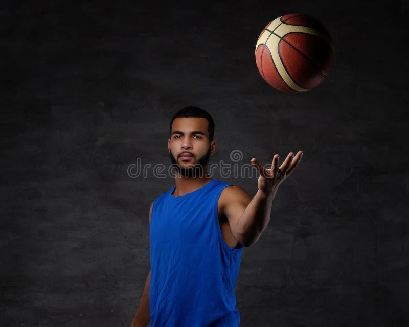 Retrato de um desportista afro-americano Jogador de basquetebol no sportswear com uma bola fotos de stock