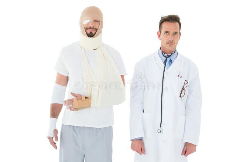 Retrato de um doutor com o paciente amarrado acima na atadura imagens de stock