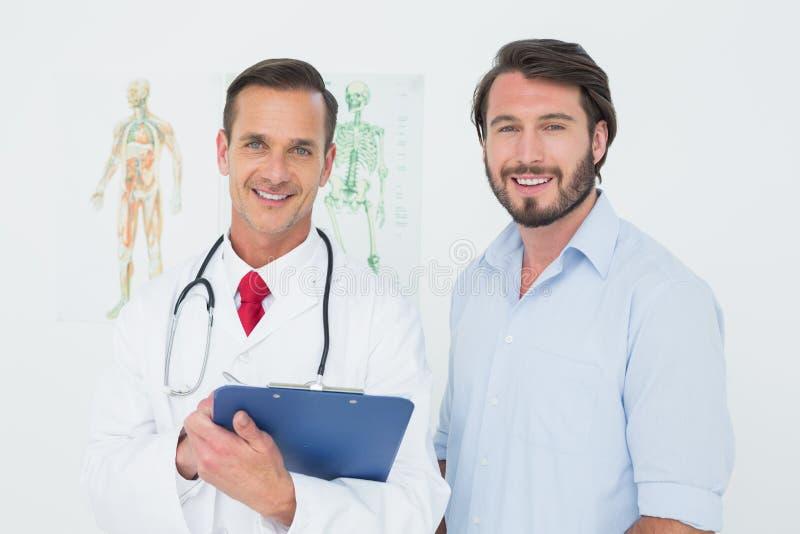 Retrato de um doutor e de um paciente masculinos com relatórios foto de stock