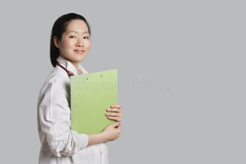 Retrato de um doutor fêmea asiático seguro que guardara a prancheta sobre o fundo cinzento imagem de stock