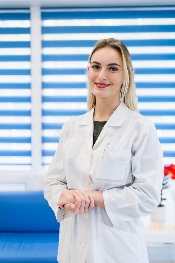 Retrato de um doutor fêmea novo que veste um revestimento branco que levanta no escritório do hospital foto de stock