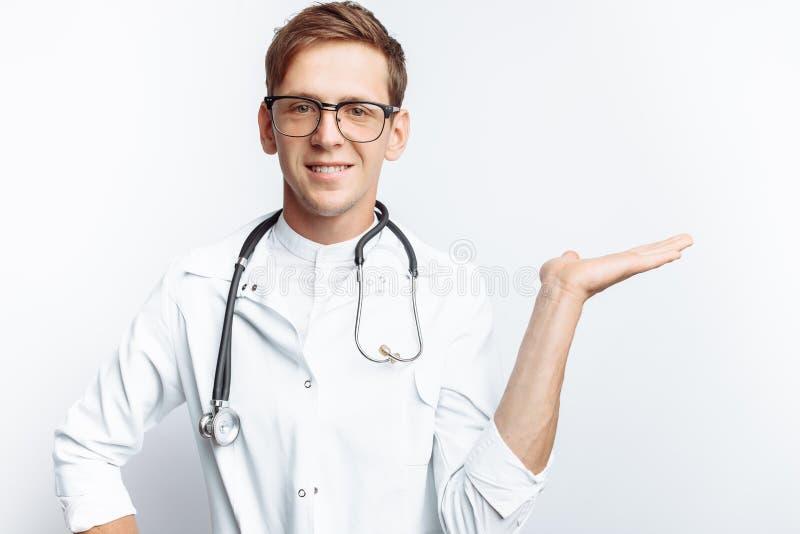 Retrato de um doutor novo, em um fundo branco, que aponte a mão a uma vista vazia, estagiário na oficina, com stethos fotos de stock royalty free