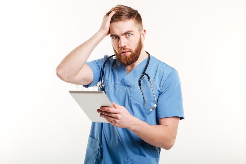 Retrato de um doutor novo surpreendido no uniforme azul imagem de stock royalty free
