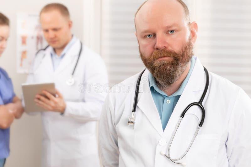 Retrato de um doutor real seguro que está na frente de sua equipe da saúde imagens de stock royalty free