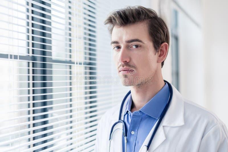 Retrato de um doutor sério novo que olha a câmera com determinação fotografia de stock royalty free