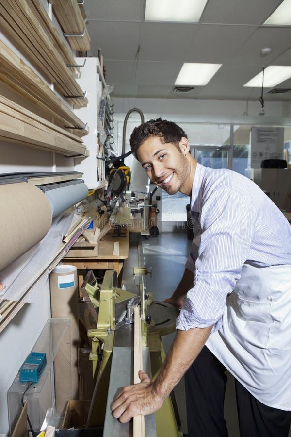 Retrato de um empregado novo que trabalha na madeira imagens de stock