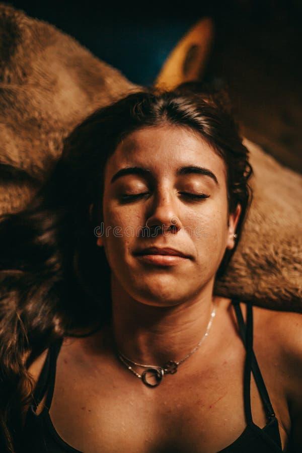 Retrato de um encontro moreno novo da mulher relaxado na cama fotos de stock royalty free