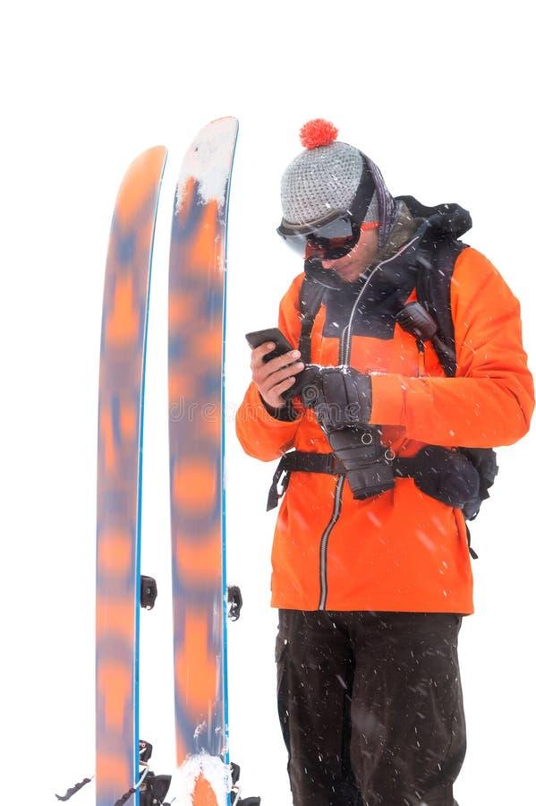 Retrato de um esquiador profissional do atleta com um telefone celular em suas mãos ao lado dos esquis isolados no fundo branco e foto de stock royalty free