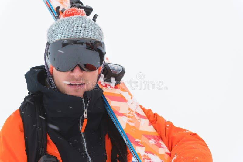 Retrato de um esquiador profissional do atleta em um revestimento alaranjado que veste uma máscara preta e com os esquis em seus  fotos de stock