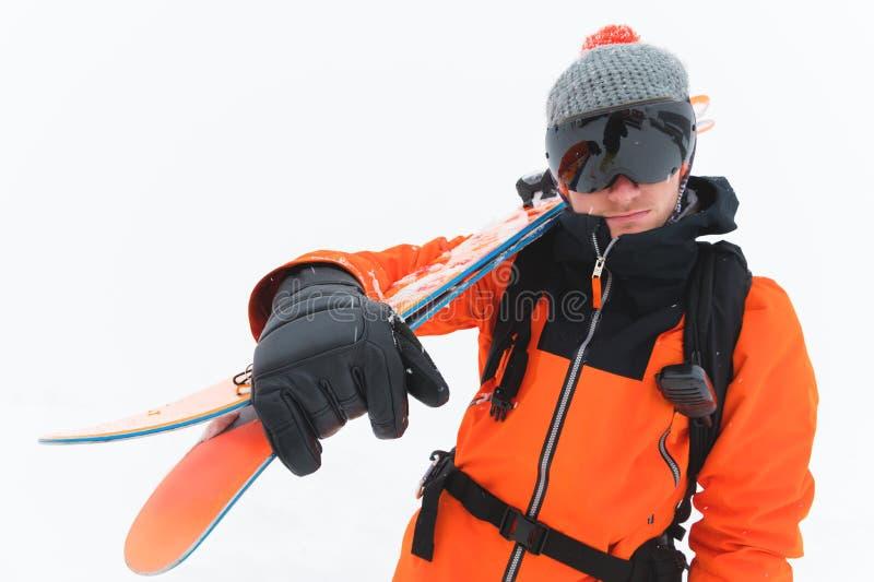 Retrato de um esquiador profissional do atleta em um revestimento alaranjado que veste uma máscara preta e com os esquis em seus  fotos de stock royalty free