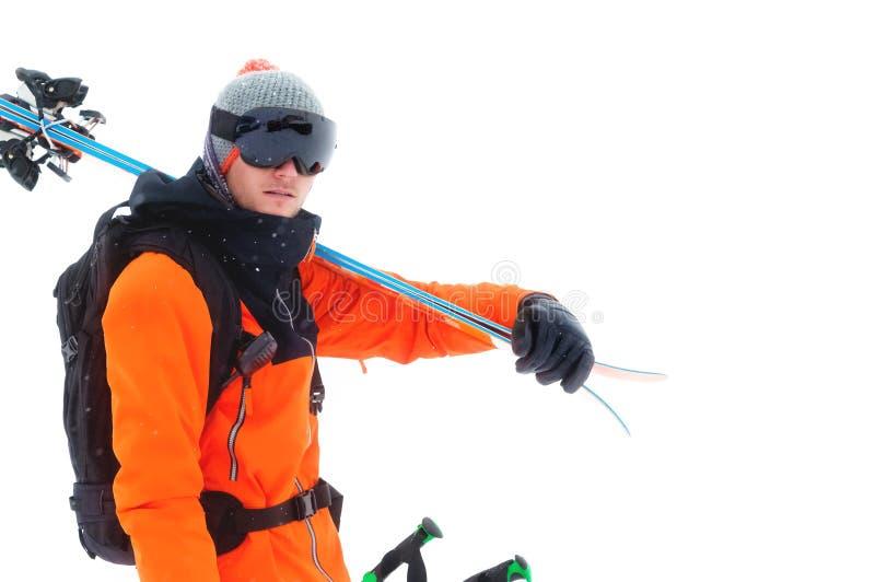 Retrato de um esquiador profissional do atleta em um revestimento alaranjado que veste uma máscara preta e com os esquis em seus  imagem de stock
