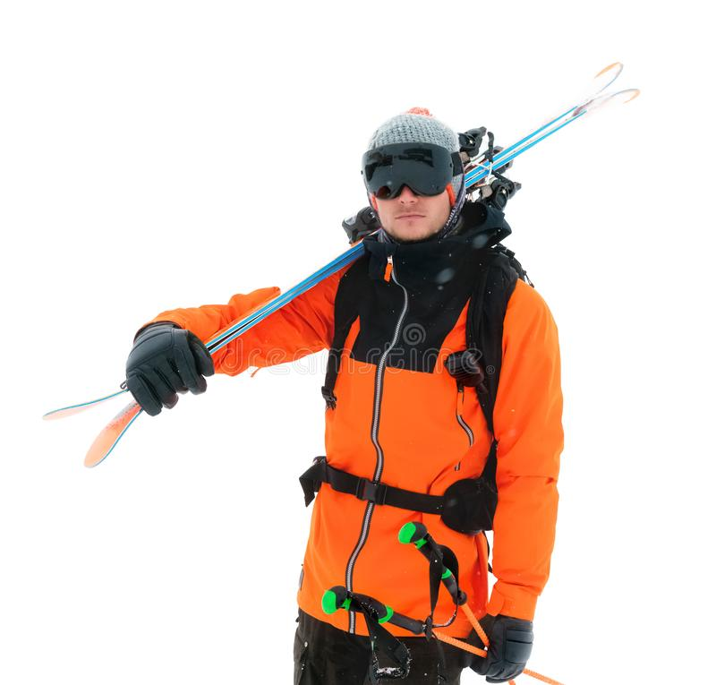 Retrato de um esquiador profissional do atleta em um revestimento alaranjado que veste uma máscara preta e com os esquis em seus  imagens de stock royalty free