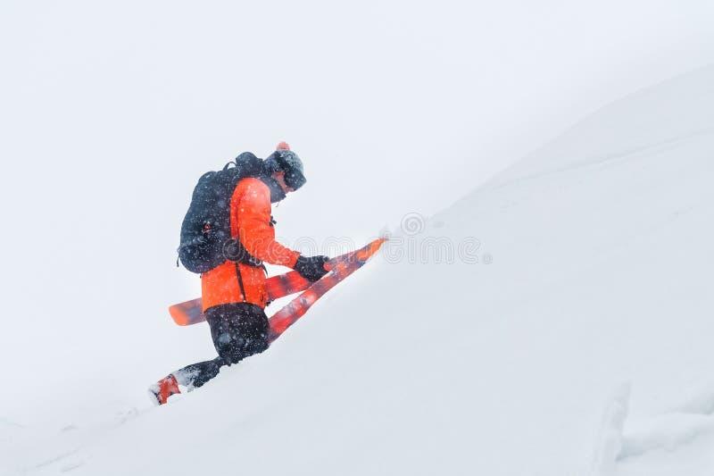 Retrato de um esquiador profissional que escala uma inclinação com céus em uma tempestade de neve O conceito da montada no mau te foto de stock royalty free