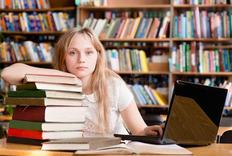 Retrato de um estudante consideravelmente fêmea na biblioteca fotos de stock