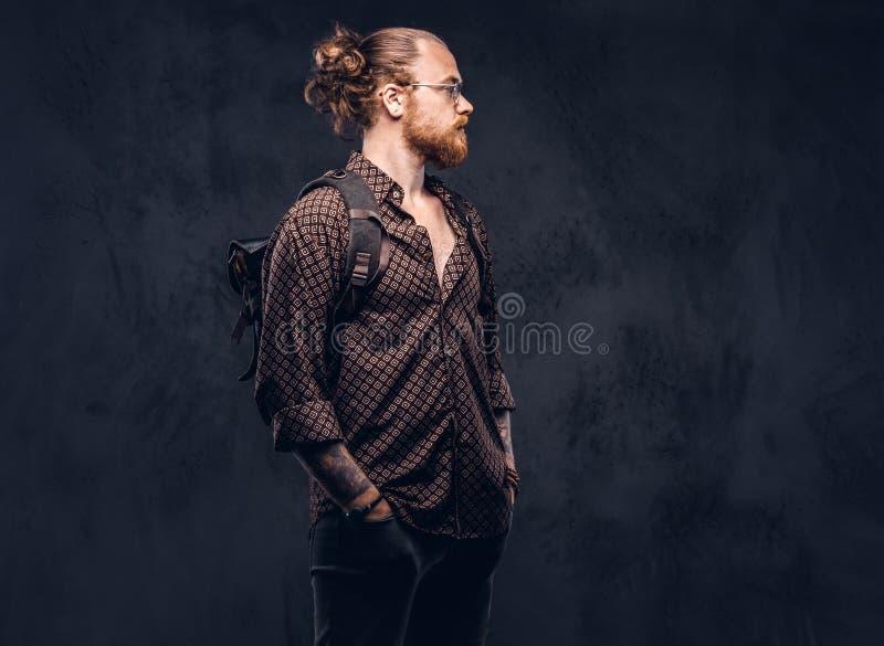 Retrato de um estudante do moderno do ruivo nos vidros vestidos em uma camisa marrom, posses uma trouxa, levantando em um estúdio imagem de stock royalty free