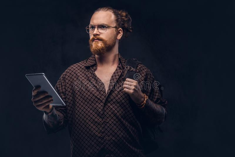 Retrato de um estudante do moderno do ruivo nos vidros vestidos em uma camisa marrom, em umas posses uma trouxa e em uma tabuleta fotos de stock