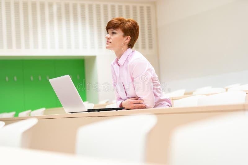 Retrato de um estudante fêmea feliz que usa o laptop na universidade Preparação para exames foto de stock royalty free