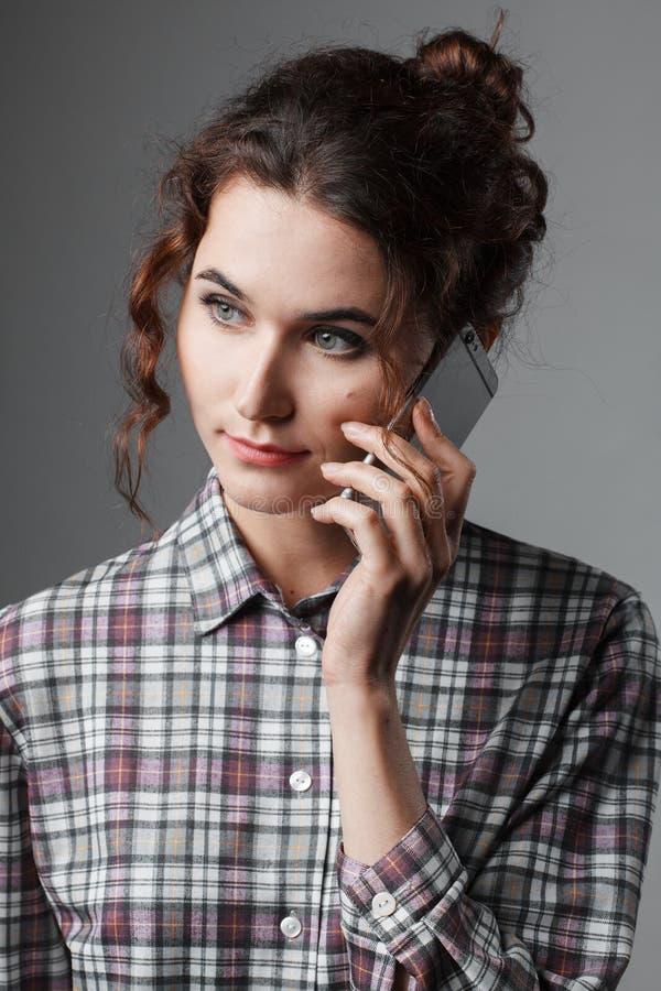 Retrato de um estudante inteligente com cabelo encaracolado e com um telefone em sua mão Camisa Checkered imagens de stock