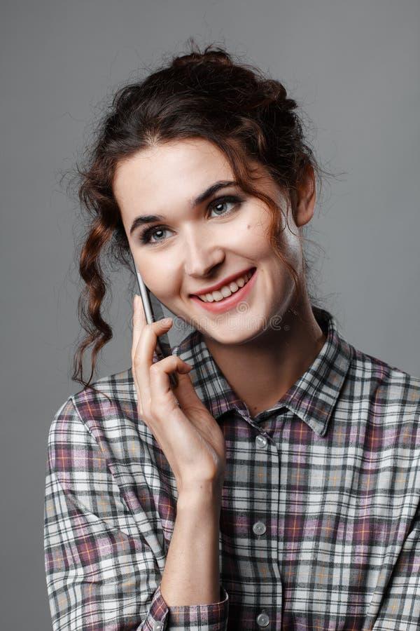 Retrato de um estudante inteligente com cabelo encaracolado e com um telefone em sua mão Camisa Checkered imagem de stock royalty free