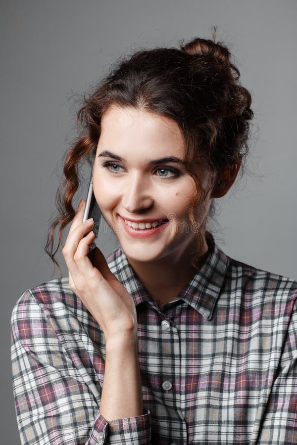 Retrato de um estudante inteligente com cabelo encaracolado e com um telefone em sua mão Camisa Checkered fotografia de stock royalty free