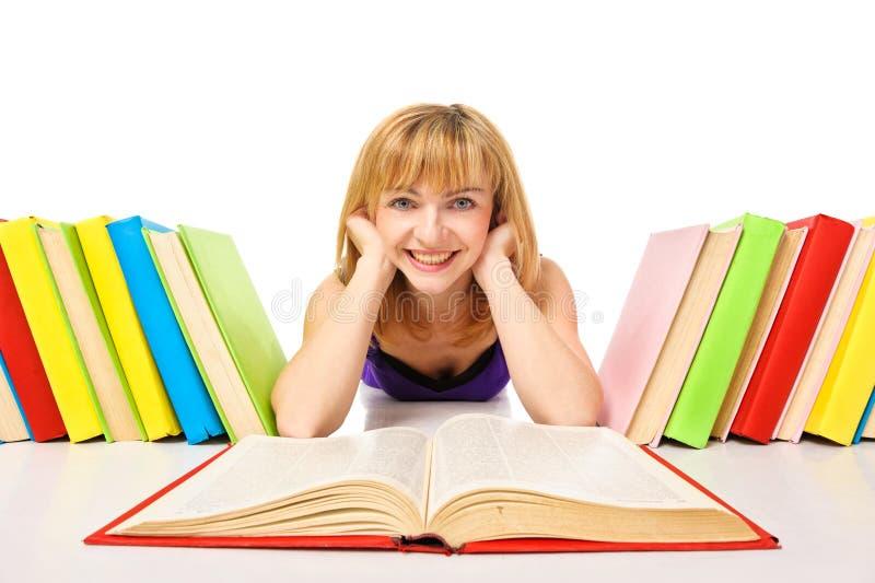 Retrato de um estudante novo que encontra-se e que lê um livro imagens de stock royalty free