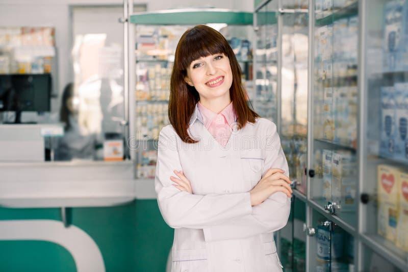 Retrato de um farmacêutico de sorriso da jovem mulher com os braços cruzados na farmácia moderna Mulher bonita que veste no labor imagens de stock royalty free