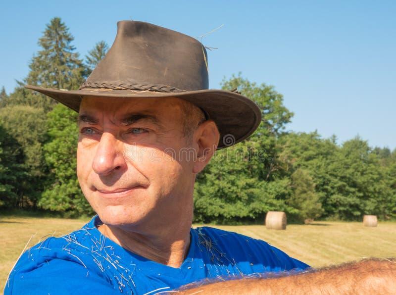 Retrato de um fazendeiro em um chapéu no campo imagem de stock royalty free