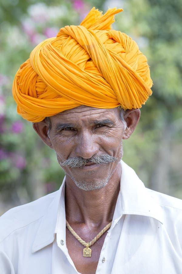 Retrato de um fazendeiro indiano que participe nos camelos favoravelmente na cidade de Pushkar de Rajasthan, Índia imagem de stock