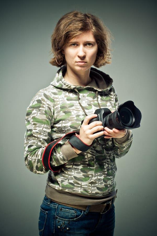 retrato de um fotógrafo que guarda a câmera retro magnífica em suas mãos macias A morena olha para cima com um relance manhoso e  imagens de stock