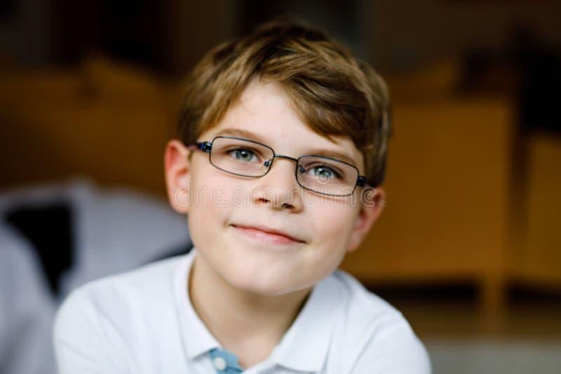 Retrato de um garoto da escola bonitinho com óculos Linda criança feliz olhando para a câmera Garoto sorridente imagem de stock royalty free