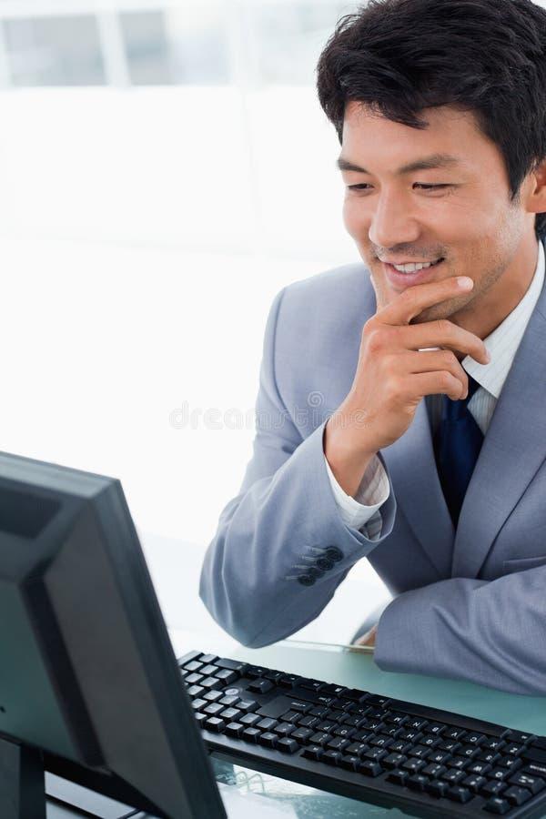 Retrato de um gerente de sorriso que usa um computador imagens de stock
