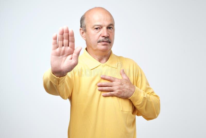 Retrato de um gesto sério da parada da exibição do homem superior com sua palma foto de stock