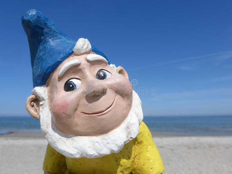 Retrato de um gnomo engraçado do jardim na frente do céu azul imagem de stock royalty free