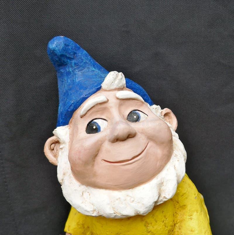 Retrato de um gnomo de sorriso do jardim com chapéu azul, a barba branca e o revestimento amarelo na frente do fundo preto foto de stock