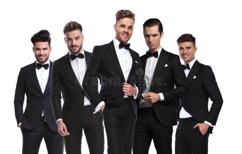 Retrato de um grupo de cinco homens elegantes em estar dos tuxedoes fotos de stock