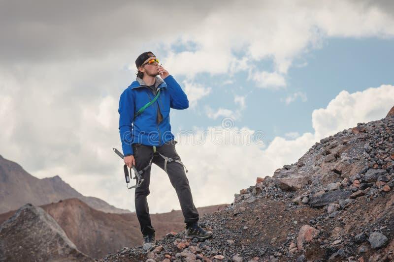 Retrato de um guia-alpinista profissional em um tampão e em óculos de sol com um machado de gelo em sua mão que fuma um cigarro foto de stock